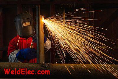 Сварщик в цеху режет металл