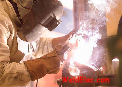 Сварщик варит электродом в перчатках