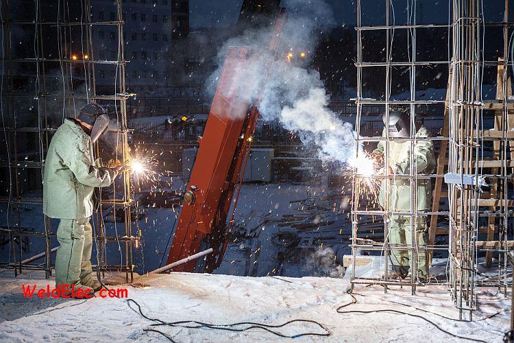 сварщики варят арматуру на стройке зимой